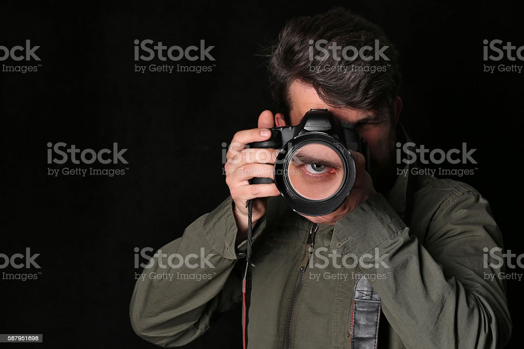 Photographer and his eye in the lens. Close up. Black stock photo