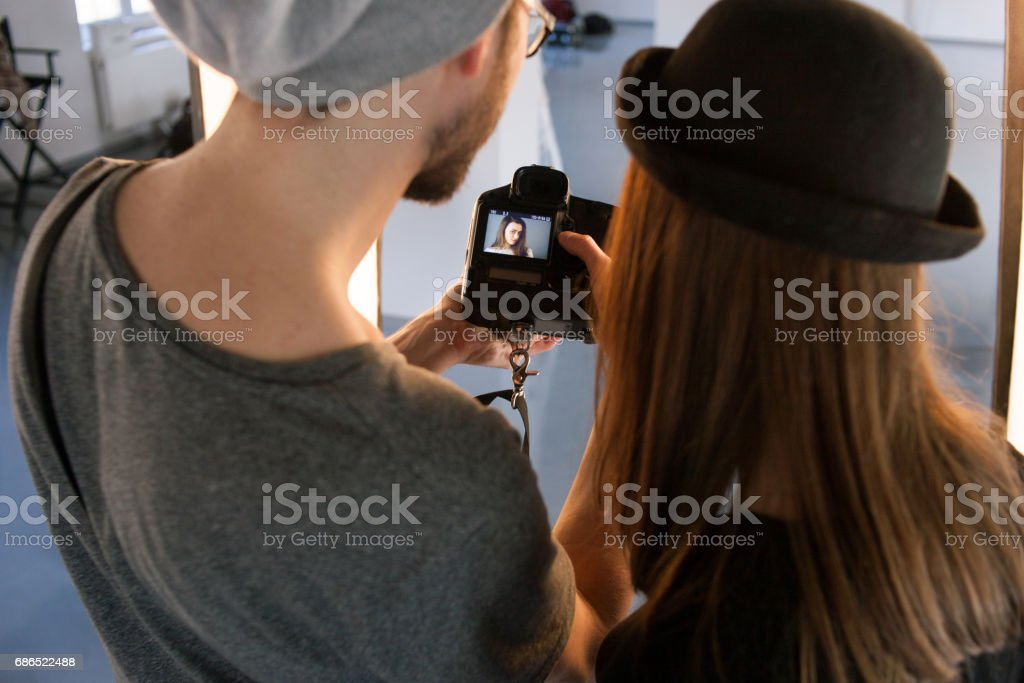 Photographer and model watching photos on camera stock photo