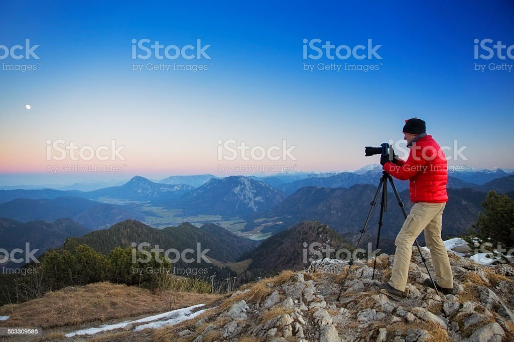 Photographer at top of a mountain in the alps stock photo