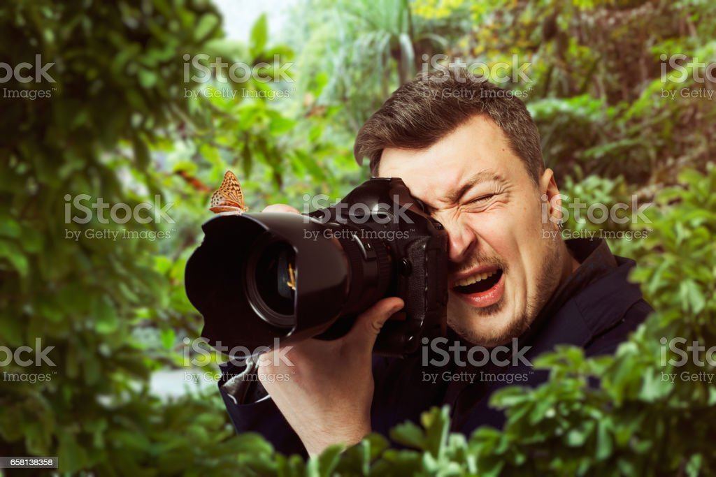 Photographer at work, butterfly on camera lens stock photo