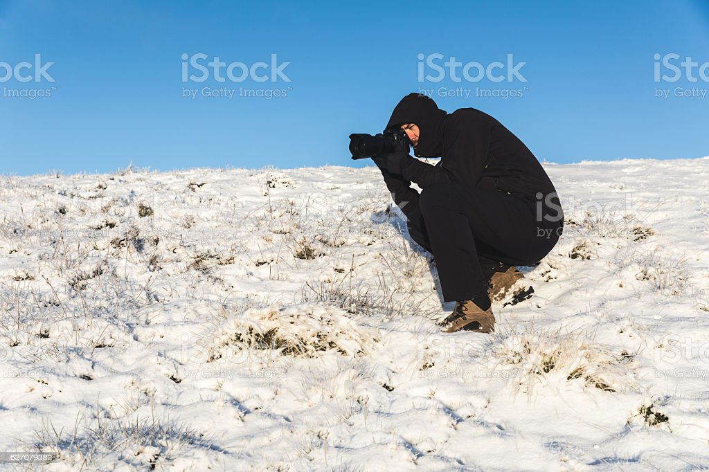Photographer at work on the snow in winter stock photo
