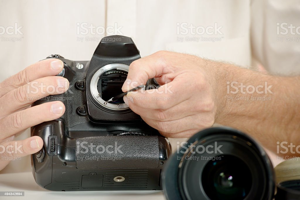 photographer cleaning sensor of his camera stock photo