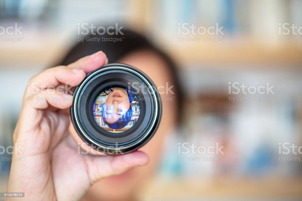 photographer holding a camera lens stock photo