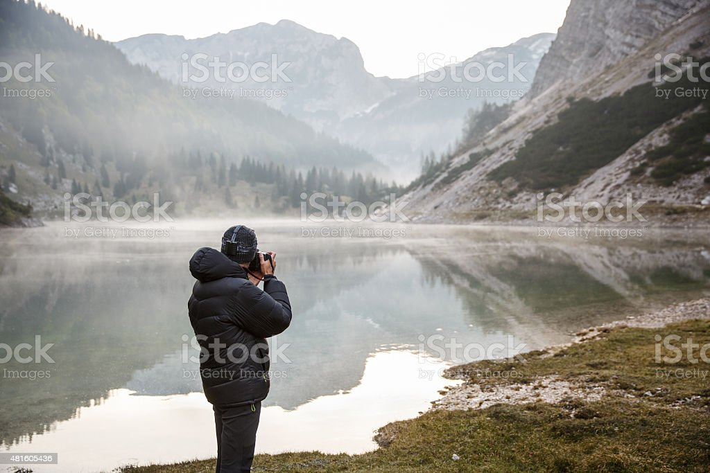 Photographer holding a camera, taking photos stock photo