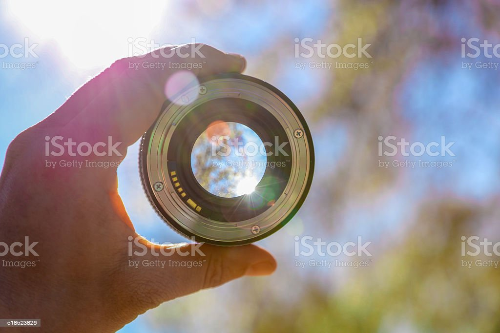 Photographer holding up lens stock photo