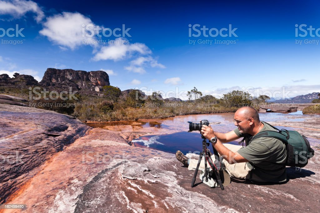 Photographer in action using tripod stock photo