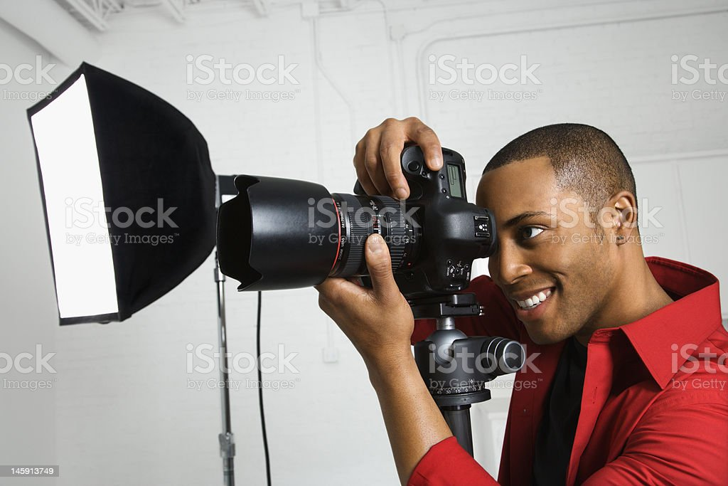 Photographer looking through camera. stock photo