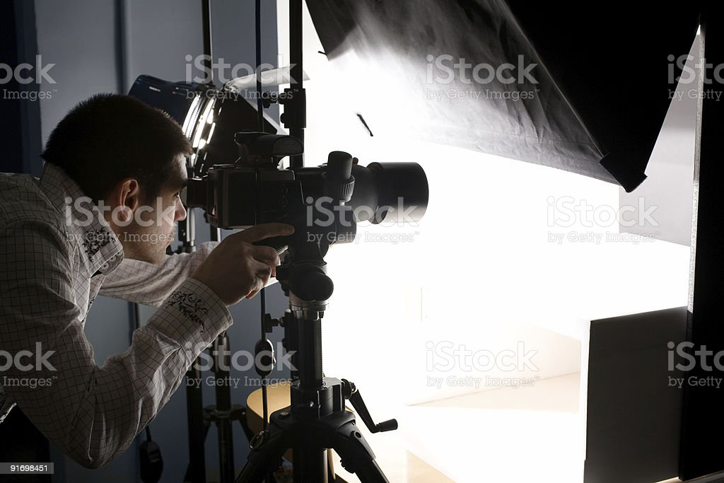 Photographer Looking Through Viewfinder Making Adjustments to Camera In Studio stock photo