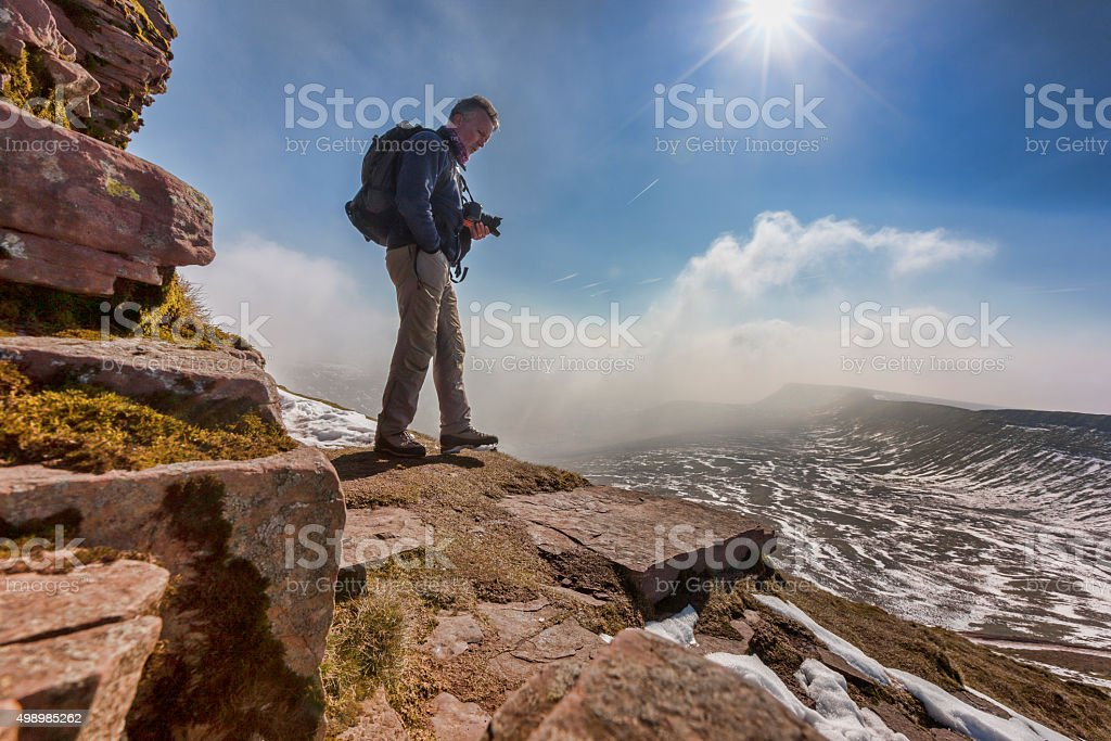Photographer on ledge of snow covered mountain stock photo