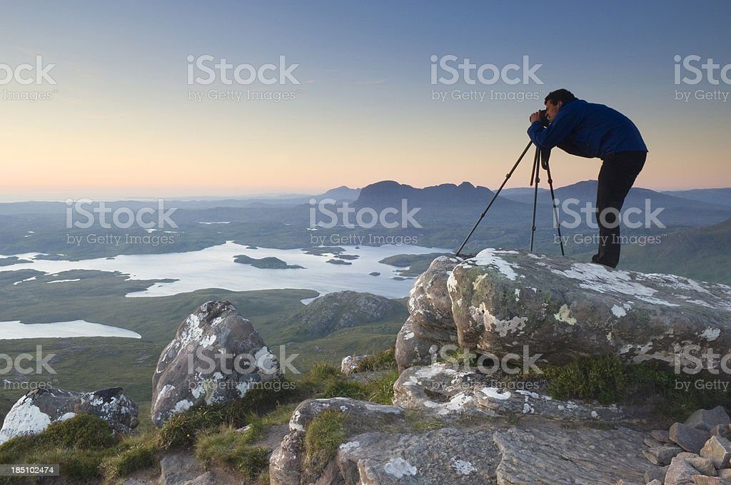Photographer on mountain top at sunset stock photo