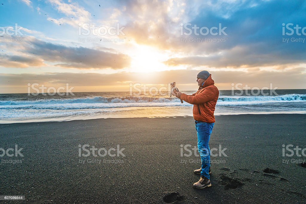 Photographer on Reynisfjara beach - black sand beach, Vik, Iceland stock photo