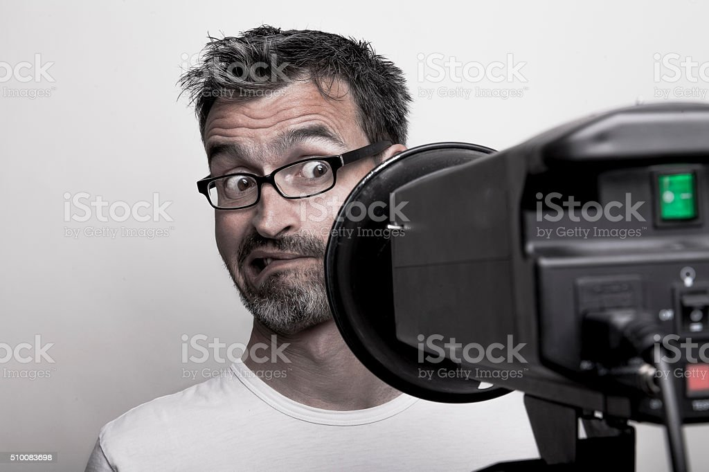 Photographer sceptically looks into a studio strobe stock photo