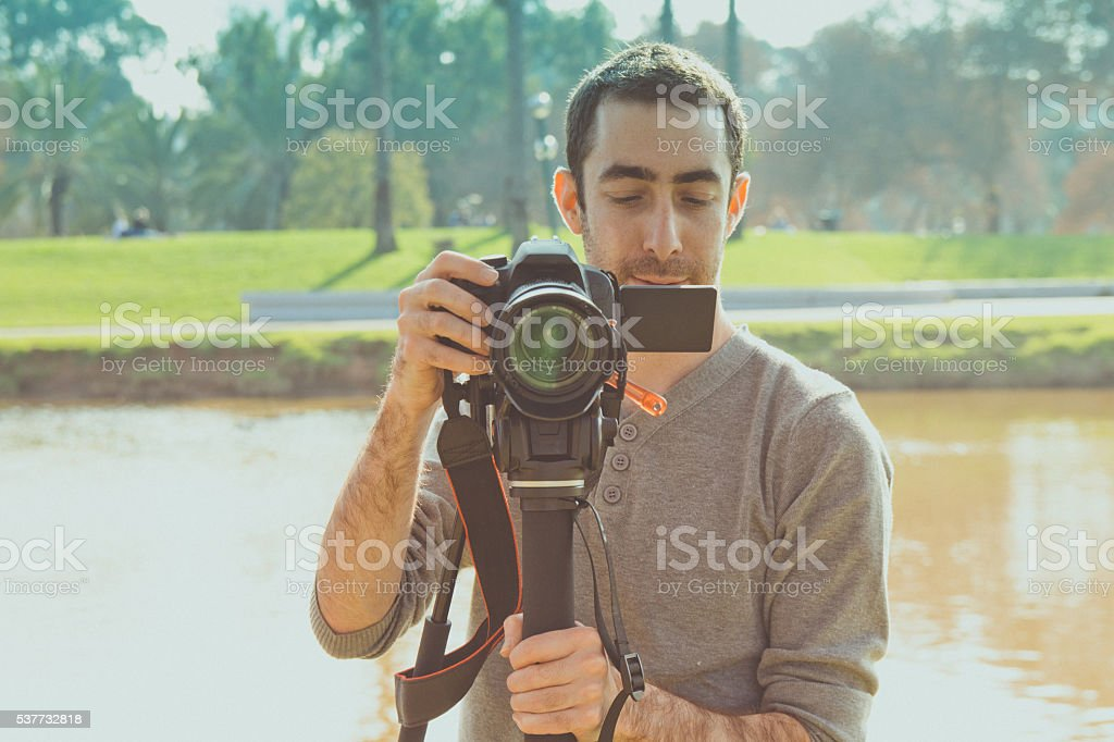 Photographer shooting outside with digital camera stock photo
