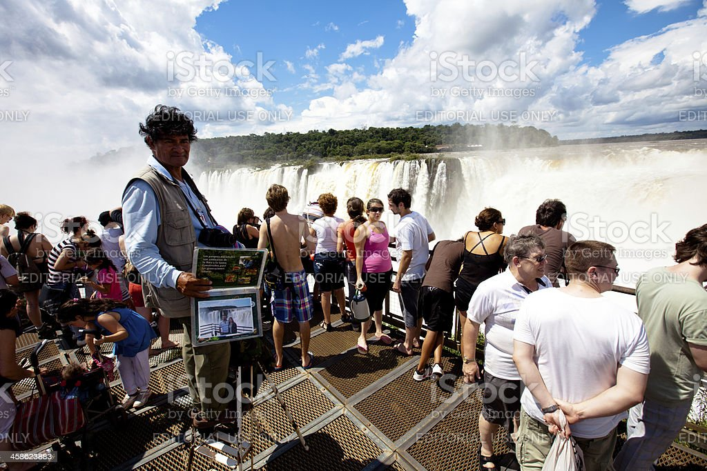 Photographer standing on a ladder at Iguazu falls royalty-free stock photo