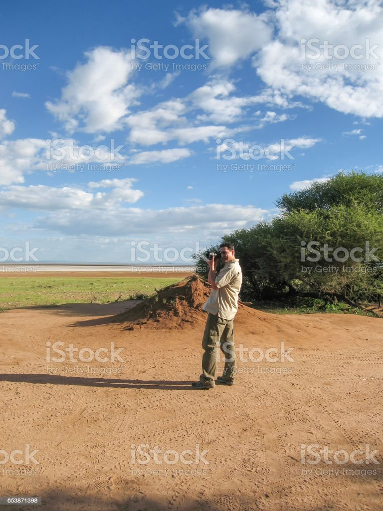 Photographer stands and takes a picture of landscape stock photo