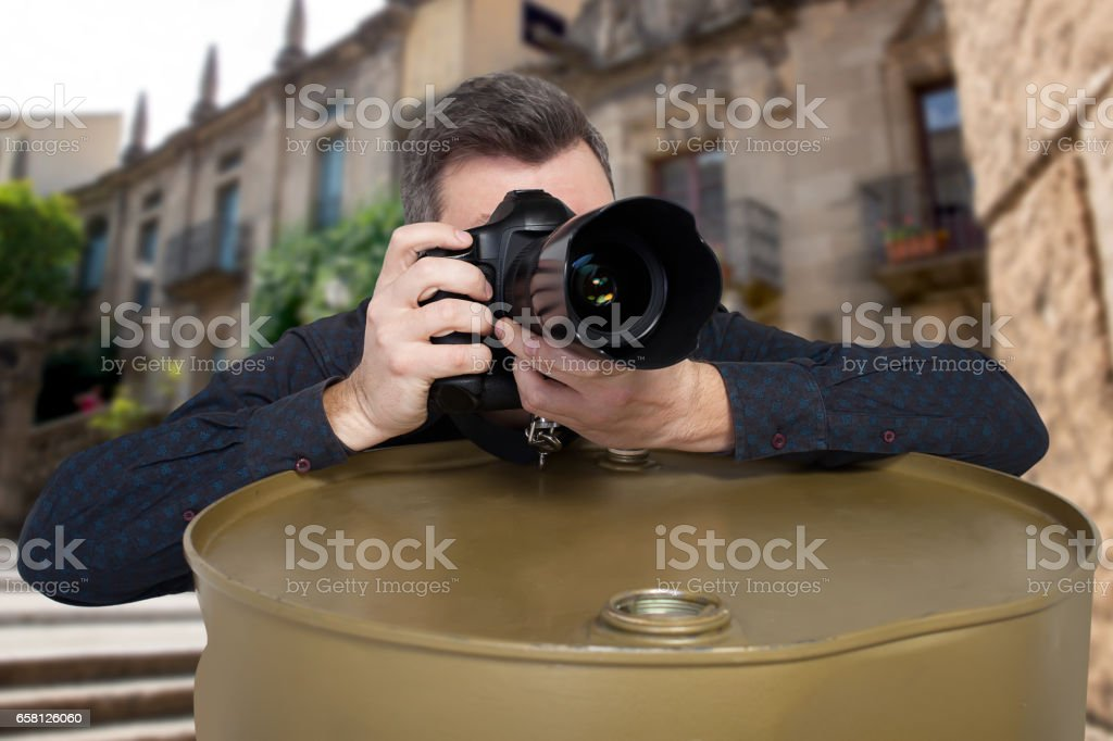 Photographer takes a picture leaning on barrel stock photo