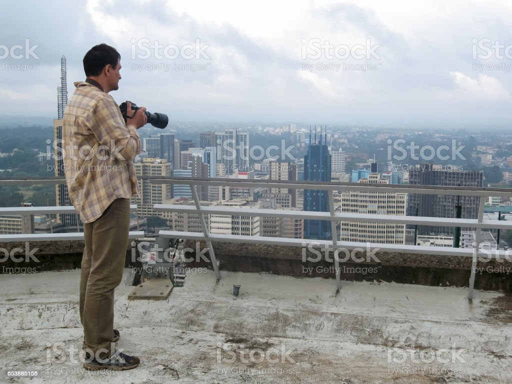 Photographer takes a picture of skyline from roof stock photo