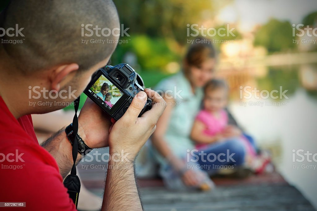 Photographer takes picture of young women with child stock photo