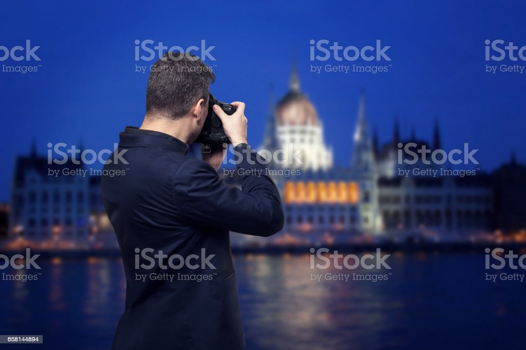 Photographer takes pictures of palace on the river stock photo