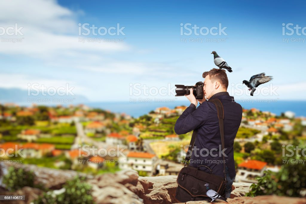 Photographer takes pucture standing on mountain stock photo