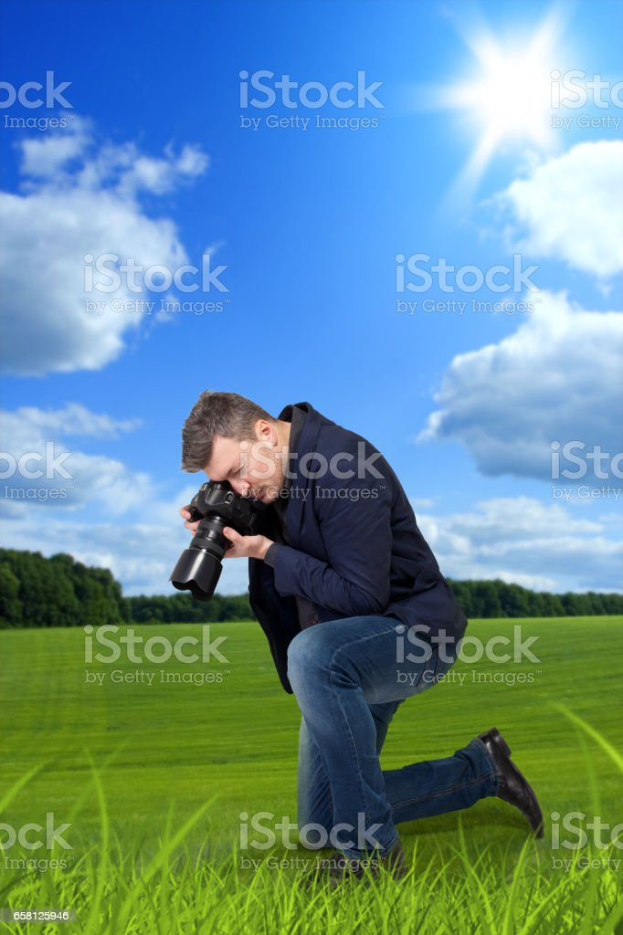 Photographer taking macro picture of green grass stock photo