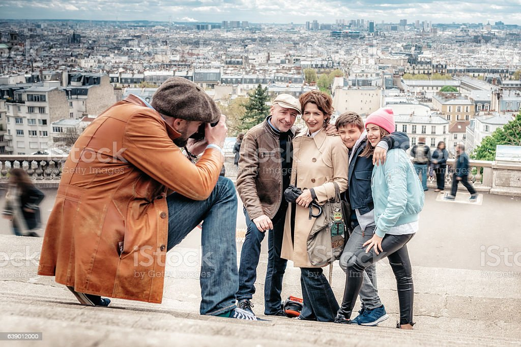 photographer taking picture of family on monmartre stairs in Paris stock photo