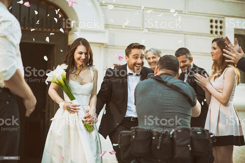 Photographer taking picture of newlywed couple stock photo