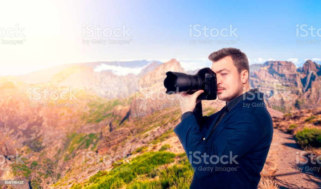 Photographer taking picture of rocky mountains stock photo