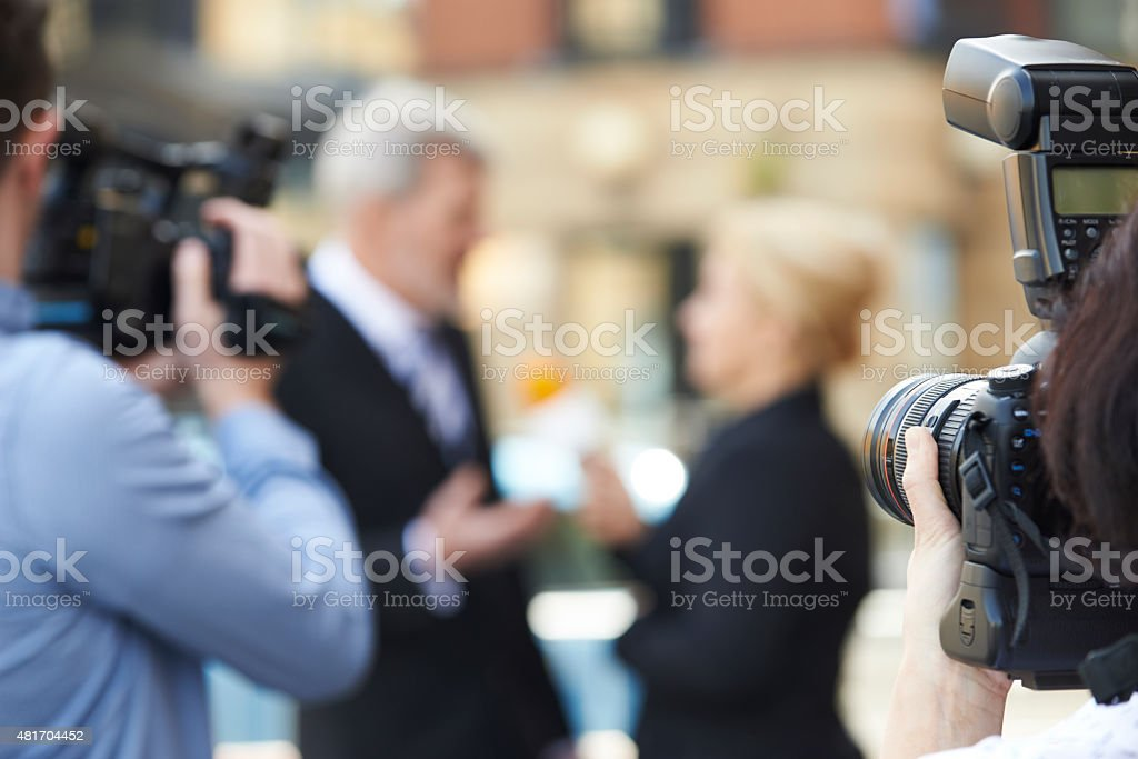 Photographer Taking Pictures Of Female Journalist Interviewing B stock photo