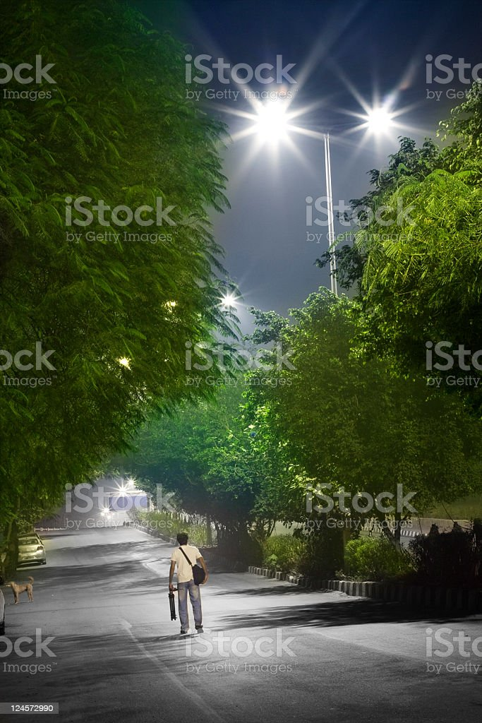 Photographer Walking on Roadside at Midnight. royalty-free stock photo
