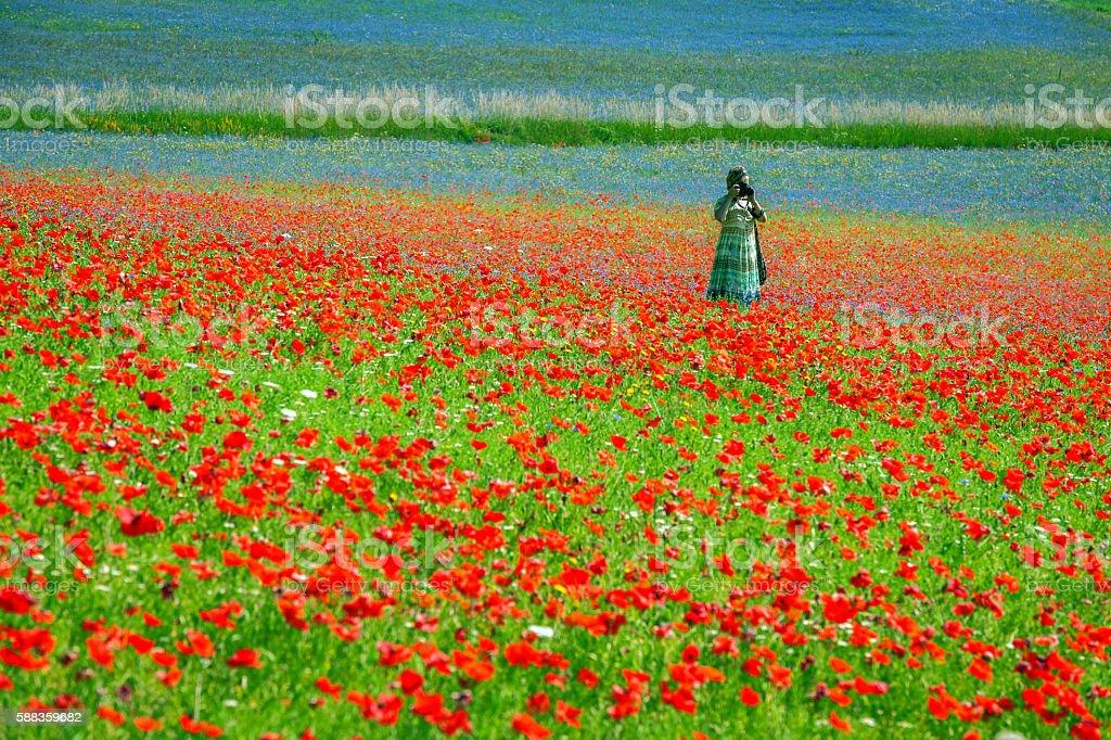 Photographer Wearing Long Green-Blue Dress near Castelluccio, Italy stock photo