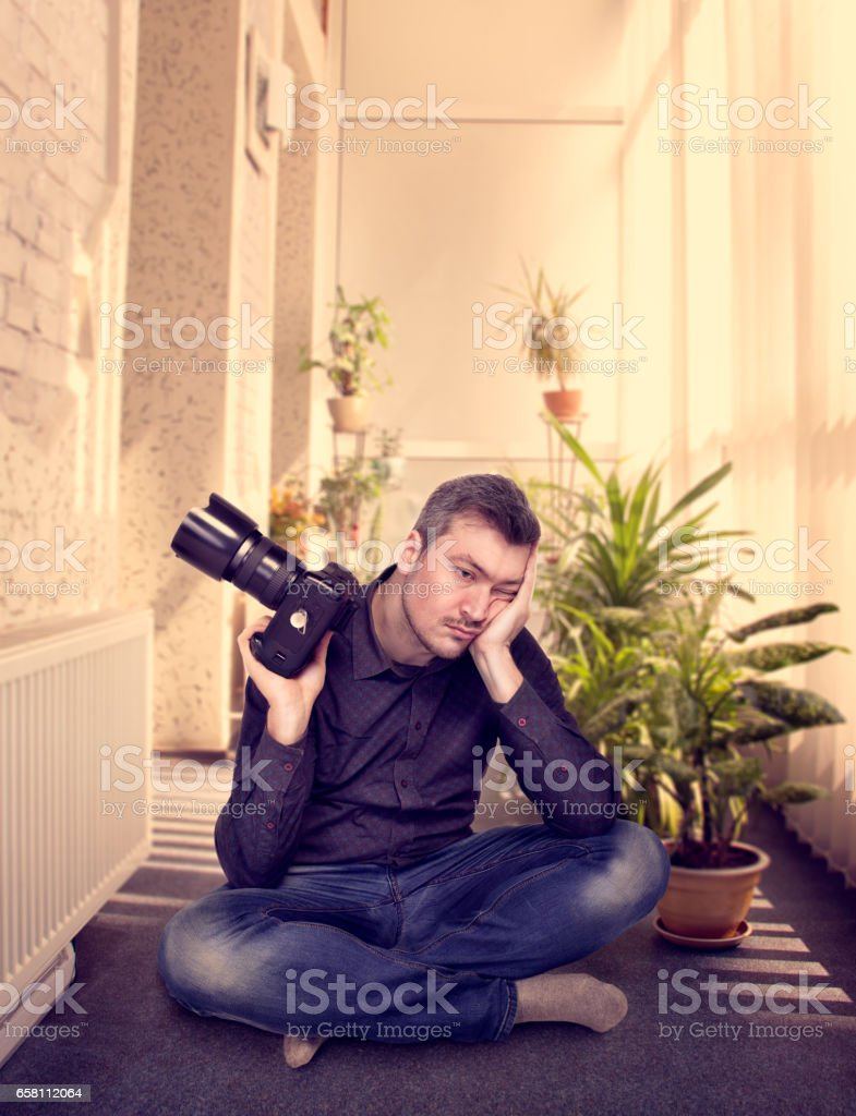 Photographer with camera sitting in a yoga pose stock photo