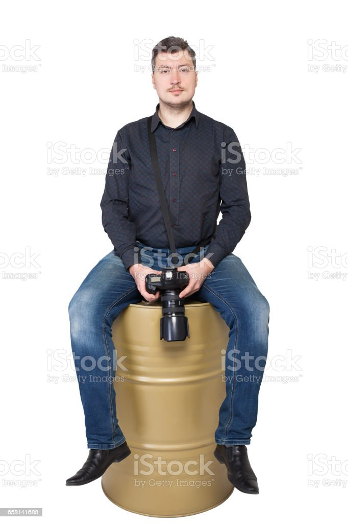 Photographer with camera sitting on an iron barrel stock photo