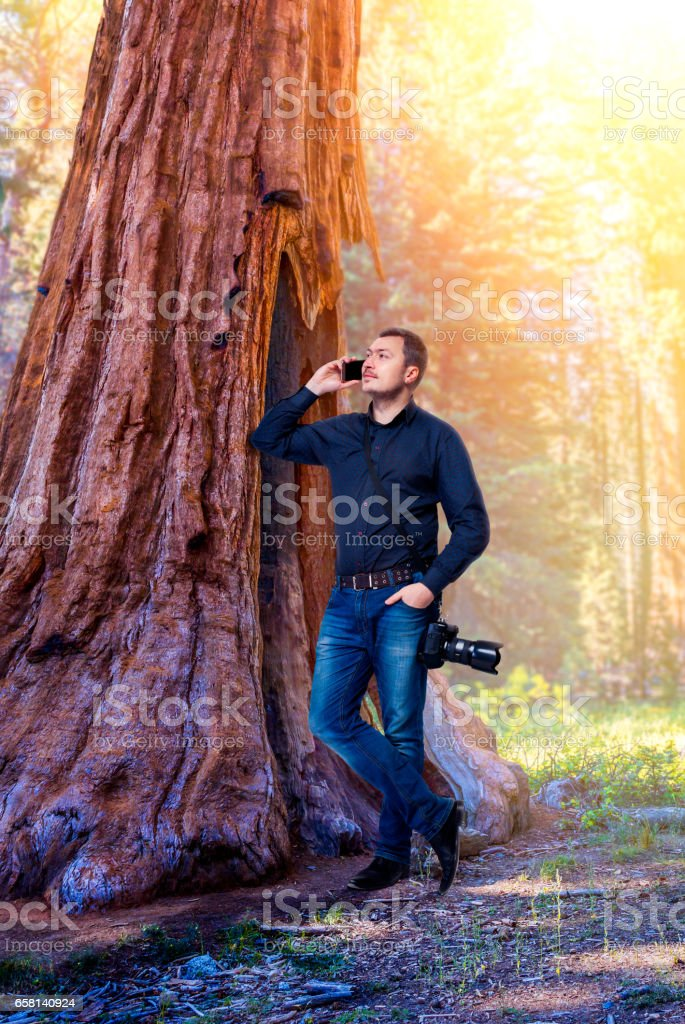 Photographer with camera talking by mobile phone stock photo
