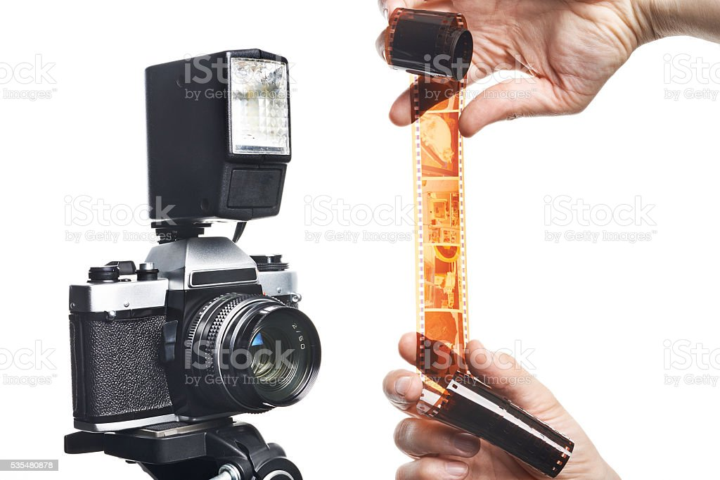 Photographer with color negative film near SLR camera isolated stock photo