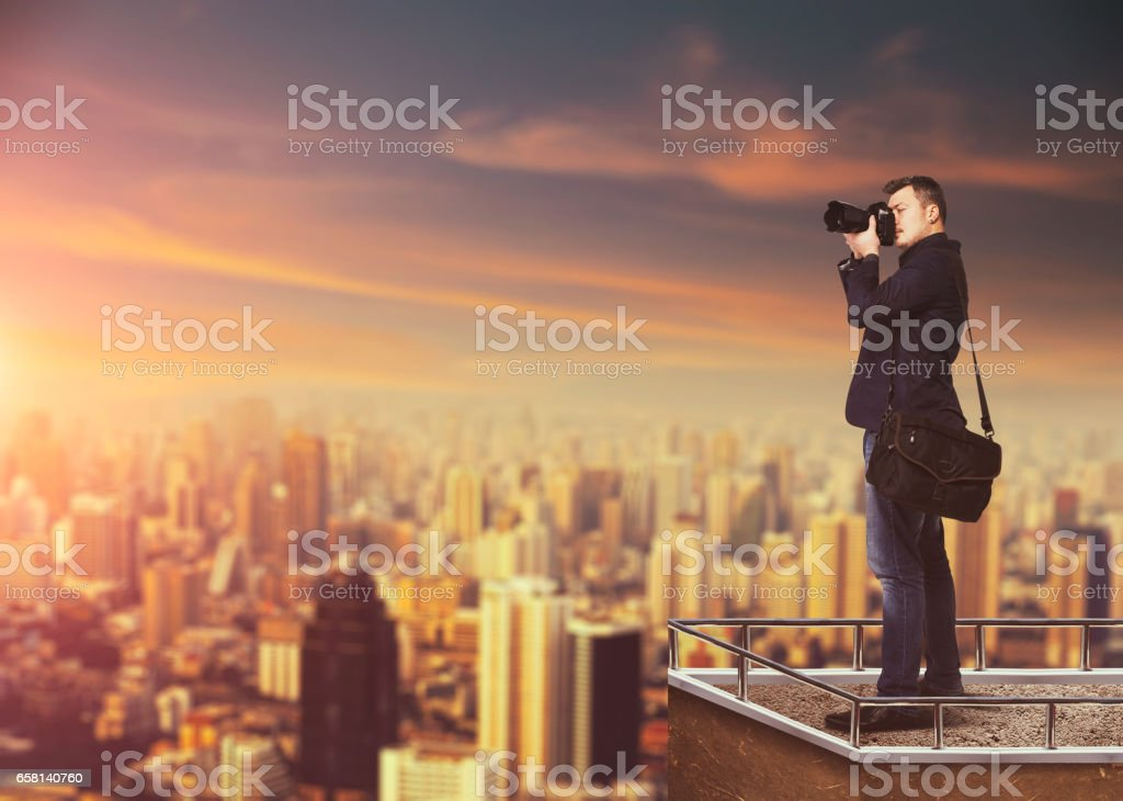 Photographer with digital camera against cityscape stock photo