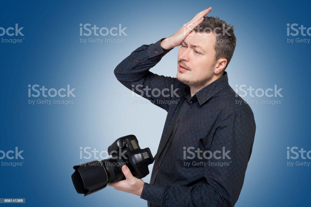 Photographer with digital camera, blue background stock photo