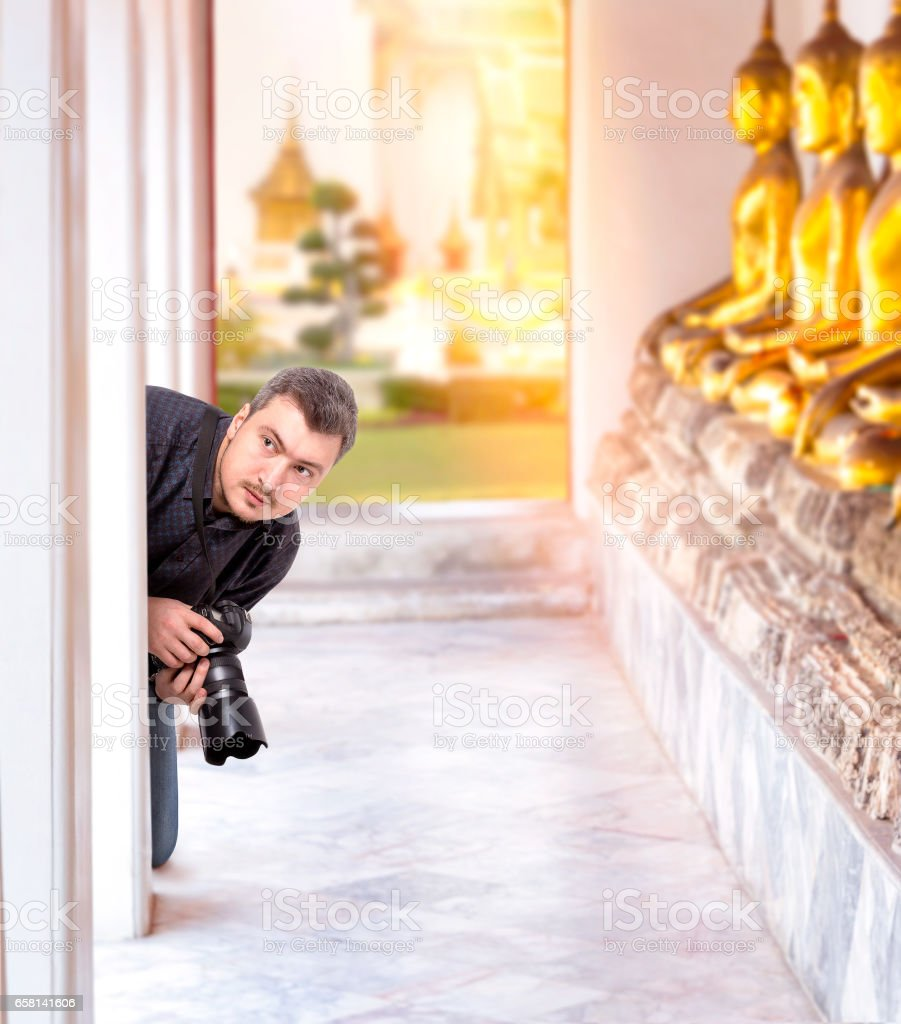 Photographer with digital camera in Buddha temple stock photo