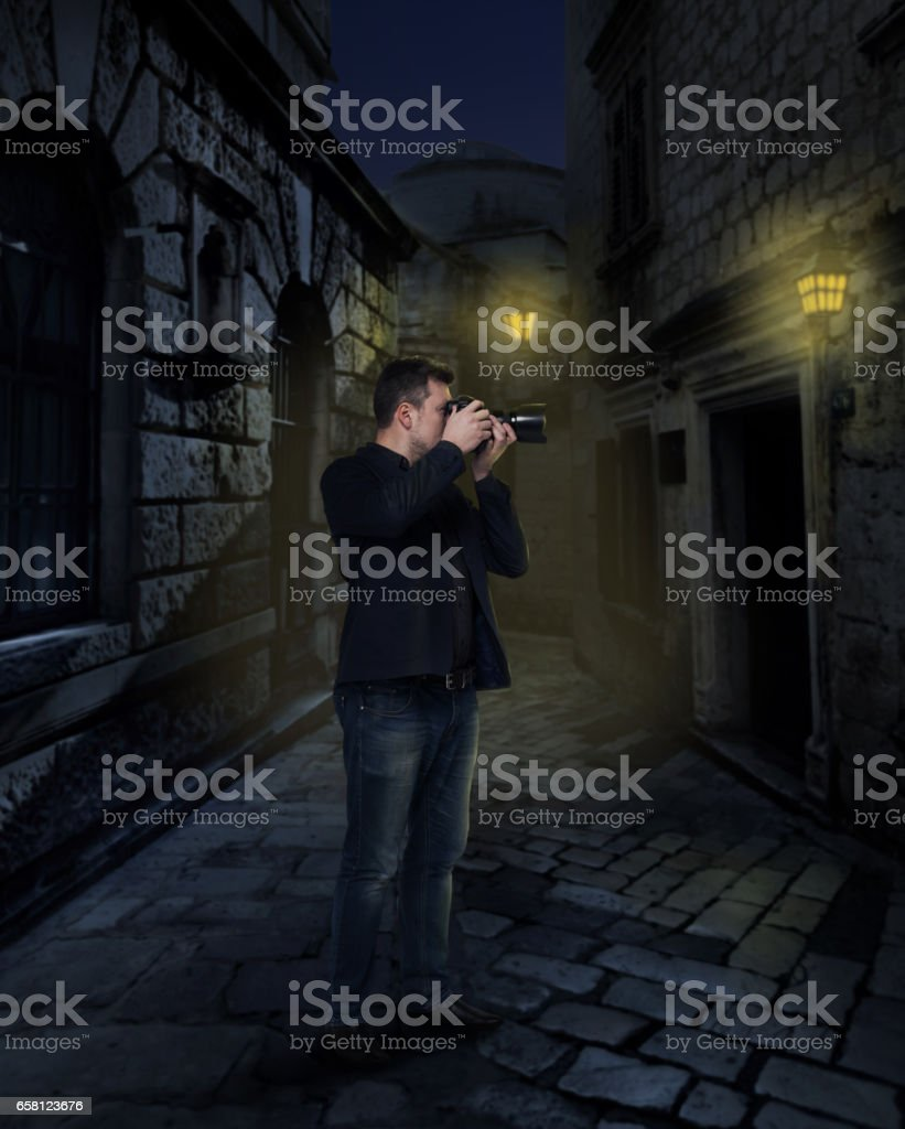 Photographer with digital camera in night alley stock photo