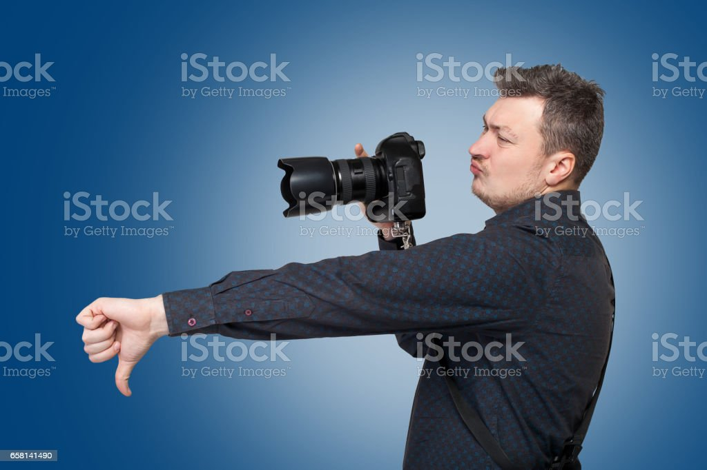 Photographer with digital camera shows thumb down stock photo