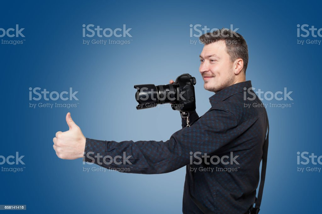 Photographer with digital camera shows thumb up stock photo