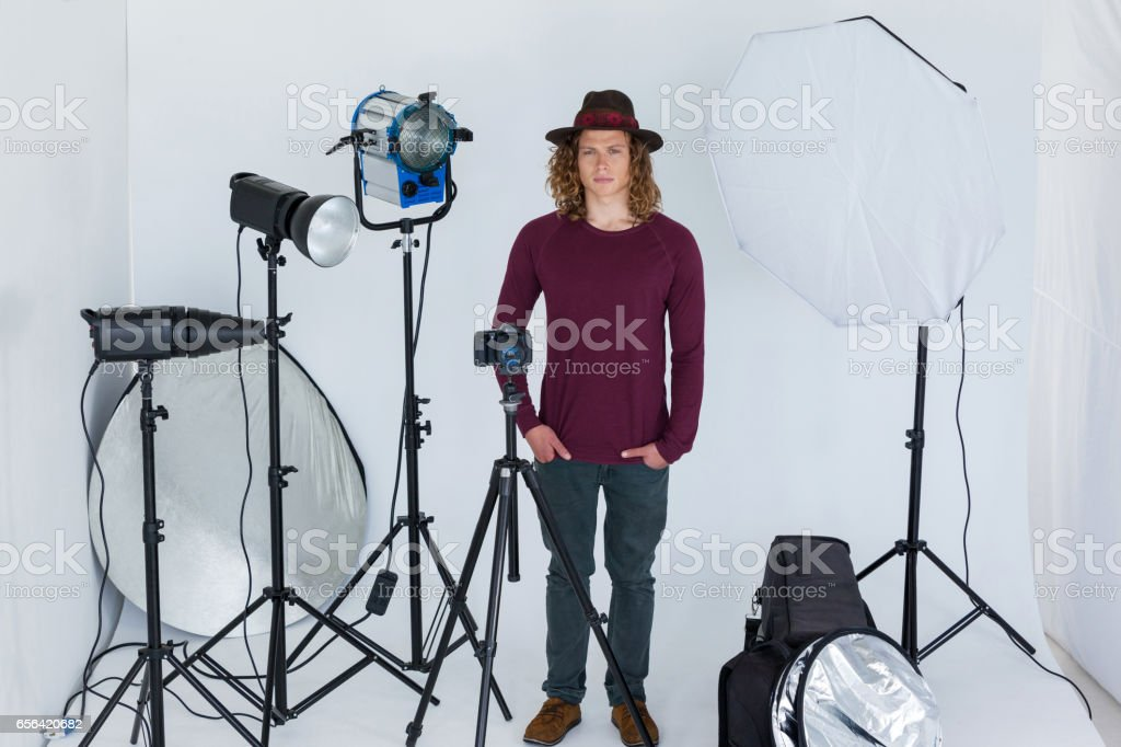 Photographer with hands in pocket standing in the photo studio stock photo