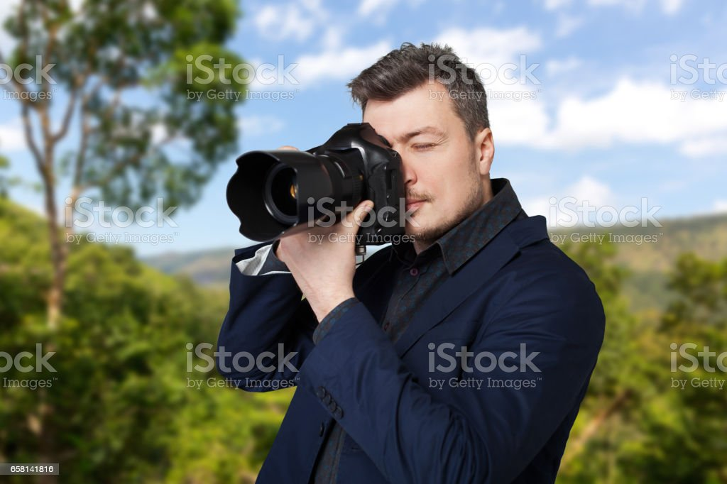 Photographer with photo camera takes the picture stock photo