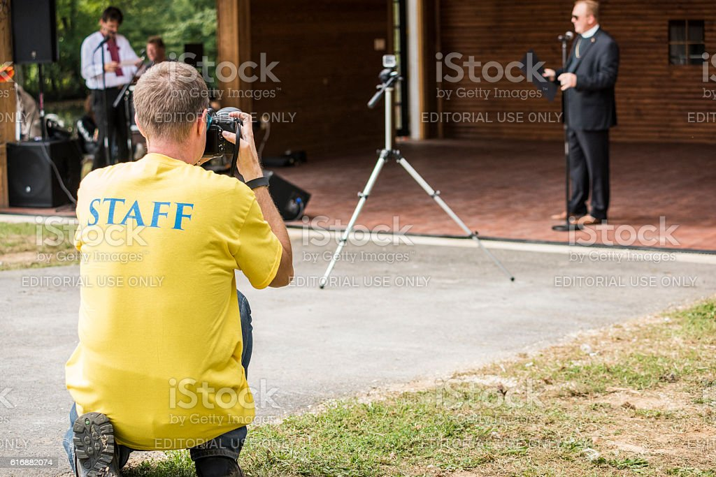 Photographer with staff text on Ukrainian flag colored shirt stock photo