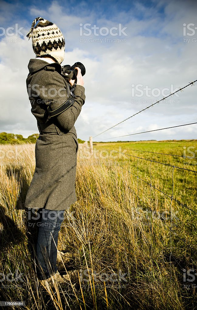 Photographer woman composing photo farm fence outdoors royalty-free stock photo
