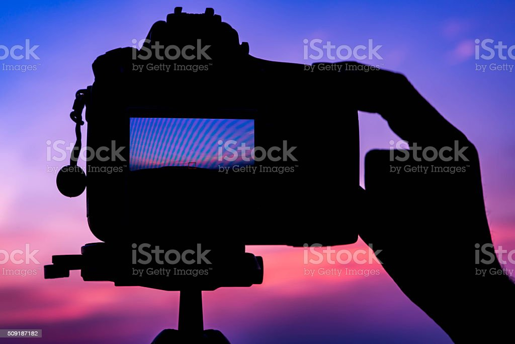 Photographer's Hand and DSLR camera focus on sunrise lanscape sc stock photo