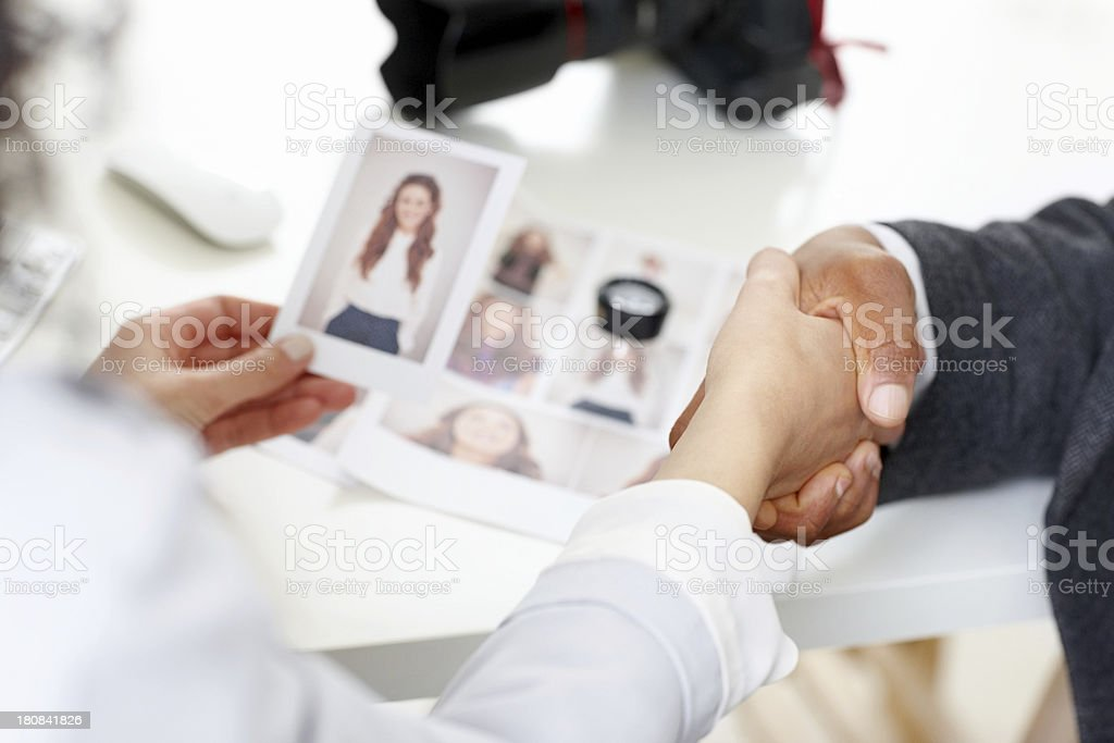 Photographers shaking hands at desk royalty-free stock photo
