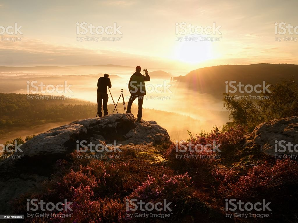 Photographers stay on cliff and takes photos. Dreamy fogy landscape stock photo