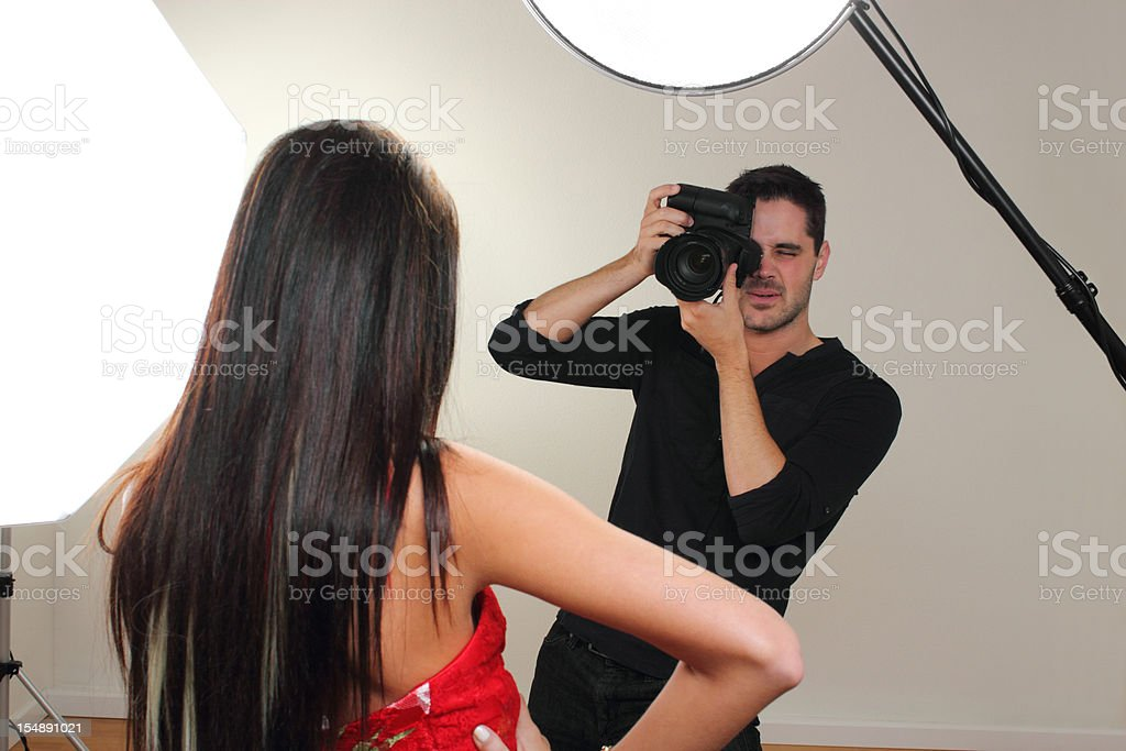XXL. Photographer shooting a fashion model in the studio.