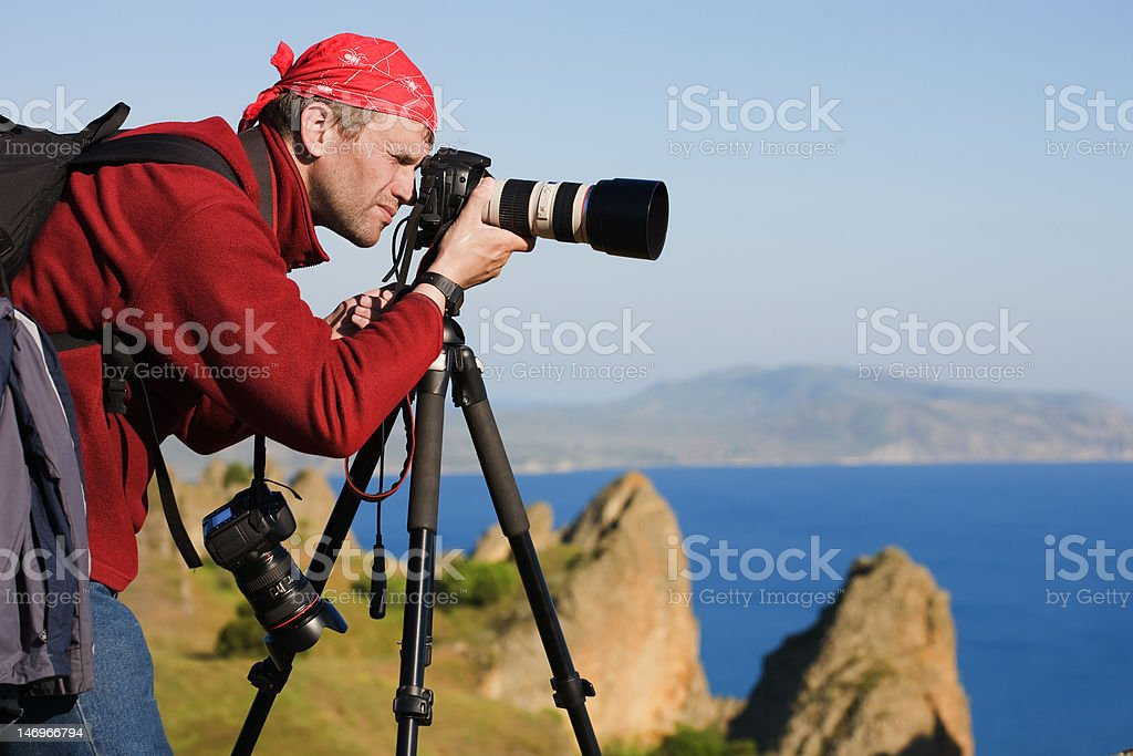 Photographer,tripod,sea,rocks stock photo